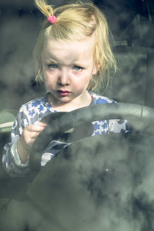 drivers seat: Portrait of blond toddler sitting behind steering wheel in a car