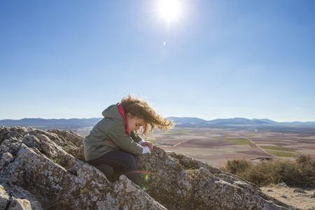 secluded: Spain, Consuegra, little girl sitting on a rock of a mountain LANG_EVOIMAGES