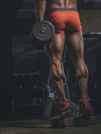 motivations: Bodybuilder training calves in gym