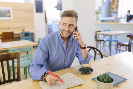 Man with newspaper sitting in a coffee shop telephoning with smartphone