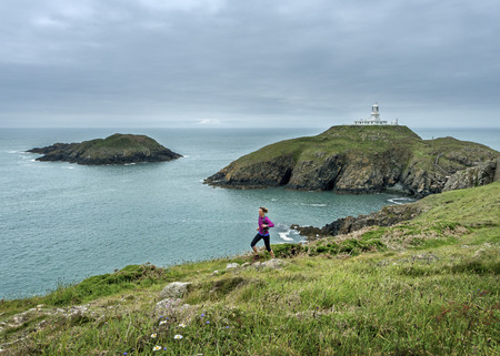 UK, Pembrokeshire, Strumble head, Mature woman running the coast path LANG_EVOIMAGES