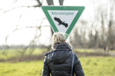 Germany, Neuss, woman in front of nature reserve sign LANG_EVOIMAGES