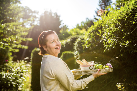 Mature woman carrying tray in garden