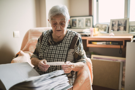 Senior woman looking at old photos of her childhood