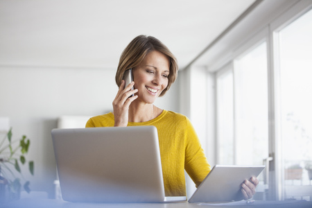 Smiling woman at home with laptop, digital tablet and cell phone