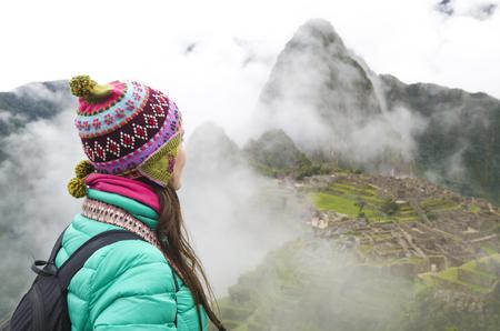 Peru, woman enjoying Machu Picchu before sunrise with the ruins surrounded by fog