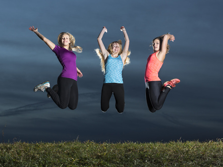 Three young women jumping together in the air