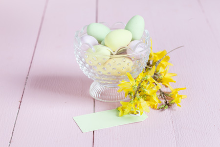 Glass bowl with sweet Easter eggs and Forsythia twig