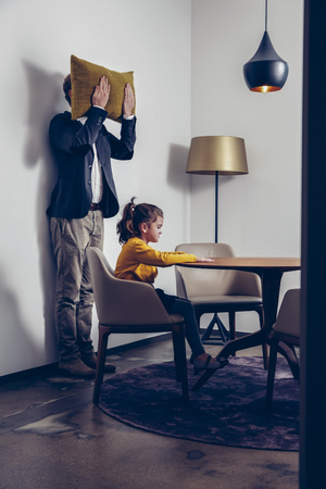 careless: Girl sitting at table with father standing at a wall covering his face with a cushion LANG_EVOIMAGES