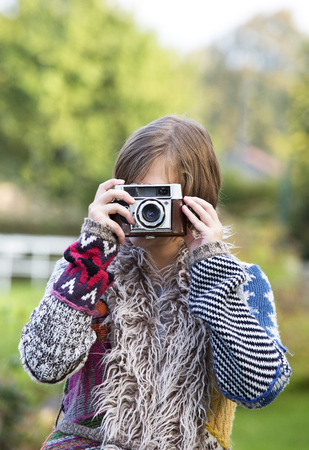 Young woman taking a picture of viewer with an old camera LANG_EVOIMAGES