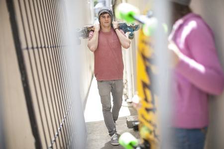 Friends with skateboards in a passageway