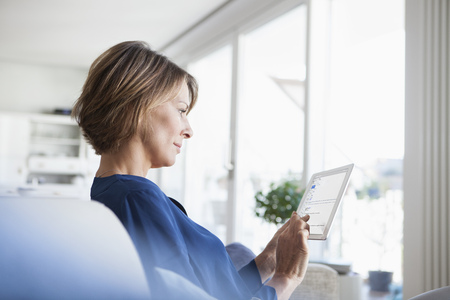 Woman at home sitting on couch using digital tablet LANG_EVOIMAGES