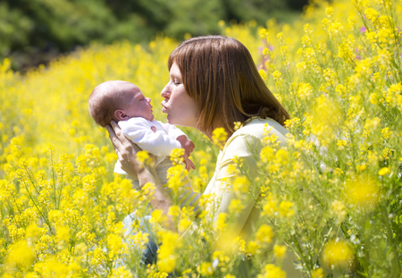 Mother with her baby girl on yellow blossoming field of flowers LANG_EVOIMAGES