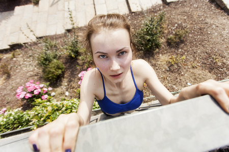 Young woman doing chin-ups on wall