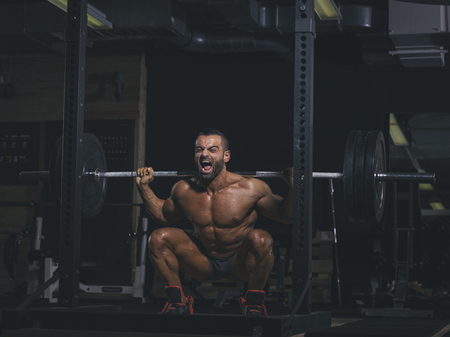 motivations: Bodybuilder performing squats with a barbell in gym LANG_EVOIMAGES