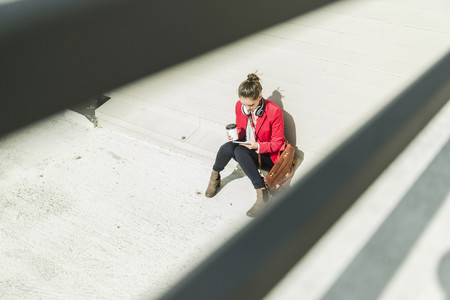 Young woman with coffee to go, headphones and phablet sitting at concrete wall