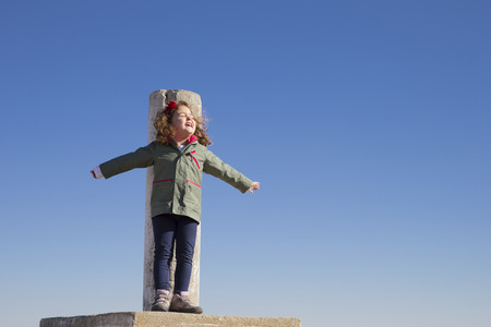mountaintops: Spain, Consuegra, happy little girl standing on summit with arms outstretched