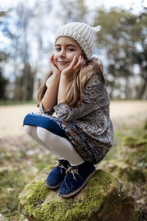 cowering: Portrait of smiling girl crouching on boulder LANG_EVOIMAGES