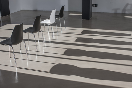 conformance: Row of chairs in empty office casting shadows