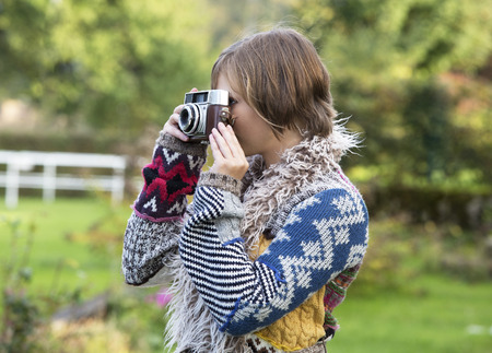 vintage: Young woman photographing with an old camera in nature