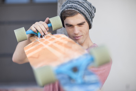 Young man scrutinizing his skateboard