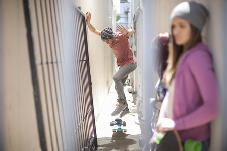 Young man doing a skateboard trick in a passageway LANG_EVOIMAGES