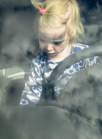 drivers seat: Blond toddler sitting behind steering wheel in a car