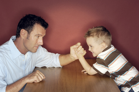 Little boy arm wrestling with his father