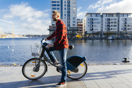 Ireland, Dublin, young man at city dock with city bike LANG_EVOIMAGES