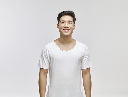 likeable: Portrait of smiling young man wearing white t-shirt LANG_EVOIMAGES