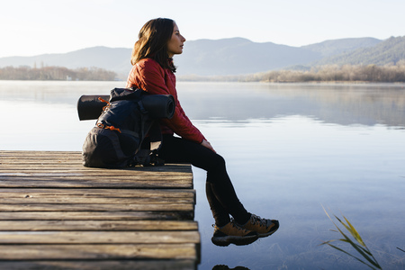 Spain, Catalunya, Girona, female hiker resting on jetty at a lake enjoying the nature LANG_EVOIMAGES