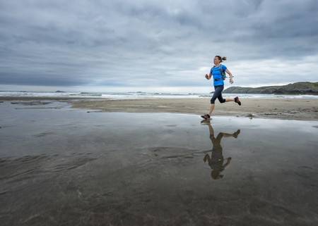 UK, Pembrokeshire, Whitesands bay, Mature woman running the coast path