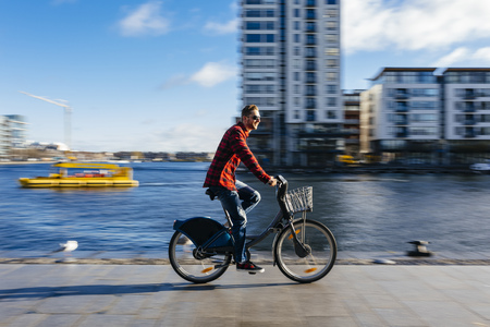 city and county building: Ireland, Dublin, young man at city dock riding city bike