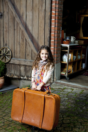 Smiling girl holding suitcase