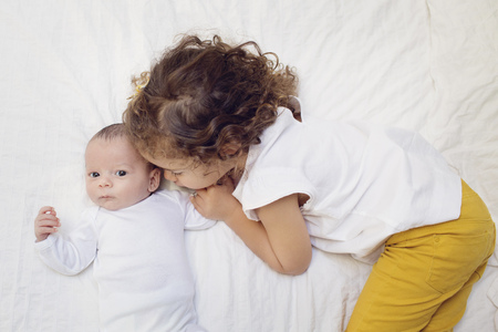 Big sister snuggling on bed with newborn brother LANG_EVOIMAGES