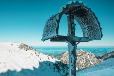 Germany, Bavaria, Chiemgau, Kampenwand, crucifix high above Chiemsee in winter