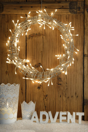 lighted: White decoration with lighted Advent wreath in front of wooden wall