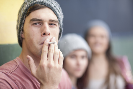 Young man with beanie smoking a cigarette LANG_EVOIMAGES