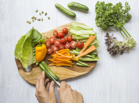 cucumis sativus: Womans hands chopping vegetables on wooden board LANG_EVOIMAGES