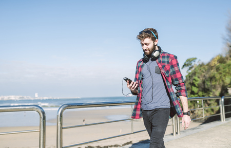 Spain, La Coruna, hipster with headphones looking at his smartphone LANG_EVOIMAGES