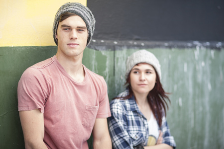 Young man and woman wearing beanies looking around