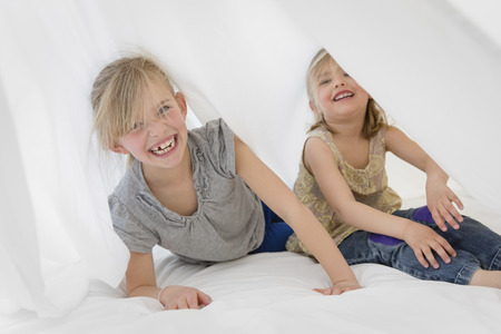 Two laughing little sisters hiding under a white sheet on a bed