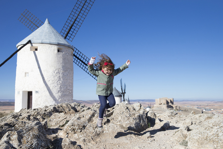 mountaintops: Spain, Consuegra, jumping little girl with windmill in the background
