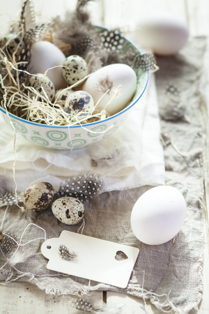 Eggs and quail eggs in bowl with tag