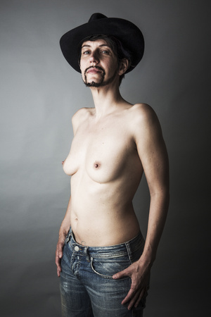 Portrait of shirtless androgynous woman with beard and hat
