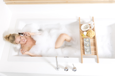 Woman on the phone in bubble bath