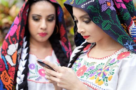 traje mexicano: Mexico, Jalisco, Xiutla dancer, folkloristic Mexican dancer with smartphone