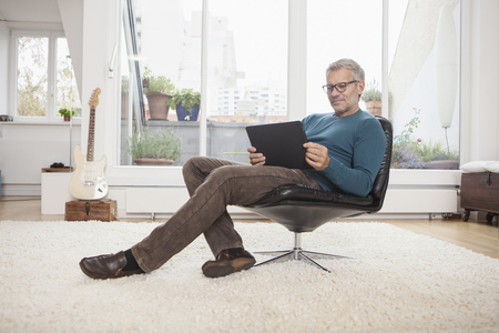Mature man at home sitting in chair using digital tablet LANG_EVOIMAGES