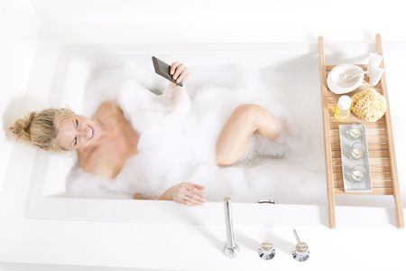 Woman looking on the phone in bubble bath