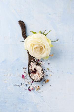White rose blossom and wooden spoon of rose lavender bath salt